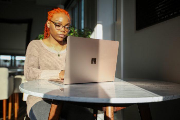 woman in beige knit sweater using Surface laptop